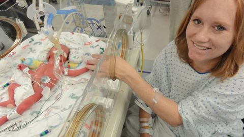 Carrie sits with one of the babies in St. Paul University Hospital's neonatal intensive care unit.