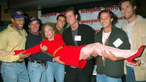 """Cosmopolitan's """"bachelor of the month"""" calendar hunks carry editor Gurley Brown into the Motown Cafe in 1996. From left: Dan Herndon, Shawn Maratea, Thom O'Brien, Kirk Williams, Vinny Lamantia and David Goldman. Gurley Brown left the magazine in 1997 to become editor-in-chief of its 64 international editions."""