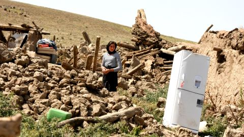 A woman stands among the debris of her destroyed home.