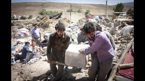 People remove belongings from collapsed buildings in Ahar in northwest Iran on Monday.