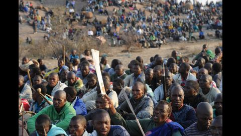 Striking mineworkers armed with machetes are monitered by a large number of police as they stage a sit-in on a hill near the mine in Rustenburg, 100 kmS (62 miles) northwest of Johannesburg on August 15, 2012, where they are demading a wage increase. Ten people were killed in clashes at the mine, which is run by leading producer Lonmin, between rival unions, the leading and decades-old National Union of Mineworkers (NUM) and the smaller Association of Mineworkers and Construction Union (AMCU). Eight Lonmin employees were killed, while two of the police officers sent to quell the unrest were hacked to death in two days of violence which started off as an illegal work stoppage on August 10 called by one of the unions. AFP PHOTO / STR        (Photo credit should read -/AFP/GettyImages)