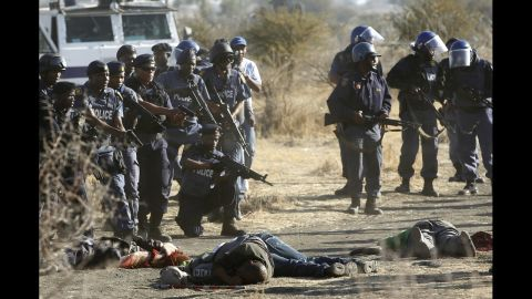 Policemen keep watch over striking miners after they were shot.
