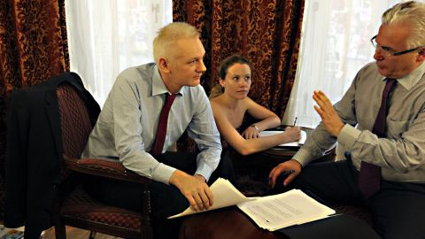 Assange talks with his legal adviser Balthasar Garcon, right, inside the Ecuadorian Embassy in London before stepping onto the balcony to make his speech.