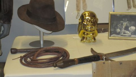 """""""Raiders of the Lost Ark"""" introduced scruffy archaeologist """"Indiana Jones"""" to the world and his trademark fedora hat and whip. In the background sits the Chachapoyan fertility idol, """"Indy's"""" removal of which literally brought the house down at the beginning of the film."""