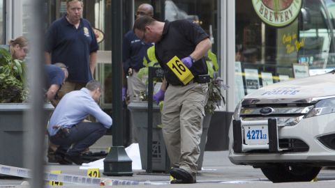 Law enforcement officers stand near the covered body of the suspected shooter on Fifth Avenue. The man opened fire outside the building's Fifth Avenue entrance, triggering a gunbattle with police, authorities said.