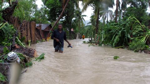 """Residents of Jacmel, Haiti, make their way through floodwaters as Tropical Storm Isaac dumps heavy rains in August 2012. An extreme exposure to climate-related events, combined with poor health care access, weak infrastructure, high levels of poverty and an over-reliance on agriculture have led to the country being categorized as at """"extreme"""" risk."""
