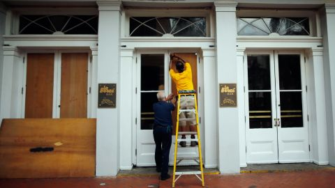 Workers place plywood on the windows of the Royal Sonesta Hotel in New Orleans on Monday to prepare for Isaac.