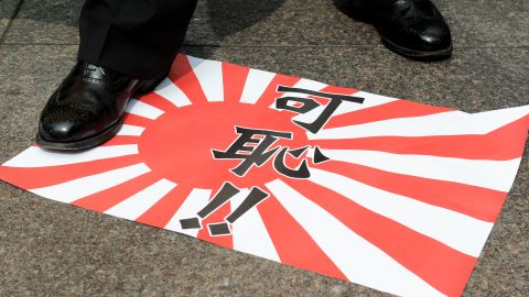 A Hong Kong activist steps on a paper replica of the Japanese imperial flag reading 'shameful' before burning it during a demonstration outside the building containing Japan's consulate in Hong Kong on August 24, 2012.  About a dozen people handed a letter over to a representative from the consulate in protest about the ongoing dispute over a group of islands, known as the Senkakus in Japanese and the Diaoyus in Chinese. Japan on August 17 deported a group of pro-Beijing activists back to Hong Kong just 48 hours after some of the 14 had become the first non-Japanese to set foot on any part of the disputed archipelago since 2004.