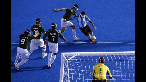 Argentina's captain Silvio Velo runs past Brazilian players to shoot at goal during the men's 5-a-side football semi-final match between Argentina and Brazil on Thursday.