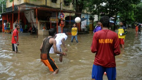 Indian residents play ball on a flooded street during heavy rains in Mumbai on August 27, 2012. The monsoon rains across the country have been more than 20% below average, sparking fears of drought among farmers who remember vividly the failure of 2009, when India suffered its worst drought in nearly four decades.