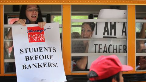 Chicago teachers display protest signs from inside a school bus as they leave a demonstration outside the Chicago Board of Education building on June 22, 2011.