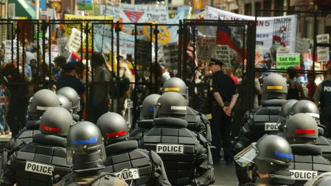 <strong>2004: </strong>Riot police stand ready inside the gates of Boston's FleetCenter, site of the Democratic National Convention, as protesters march past.