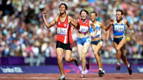 Neda Bahi of Tunisia crosses the line to win gold ahead of silver medalist Viktoriya Kravchenko of Ukraine, No. 1389, and bronze medalist Evgeniya Trushnikova of Russia, No. 1337, in the women's 400-meter T37 final on Saturday.
