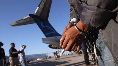 An undocumented Guatemalan immigrant, chained for being charged as a criminal is prepared for deportation.