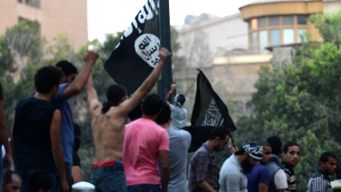Egyptian protesters raise inside the US embassy a black flag inscribed with the Muslim profession of belief: