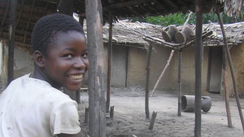 Georgette, the daughter of a local school director in Opala, DR Congo, with her pet Lesula -- the find that led biologists to identify the new species.