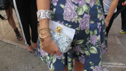 Medine carries a hard shell clutch by Reece Hudson with a chain linking it to a bracelet.