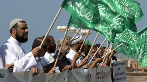 """Arab-Israeli men wave green Islamic flags with the Muslim profession of belief: """"There is no God but God and Mohammed is the prophet of God"""" during a protest in front of the U.S. Embassy on Thursday in Tel Aviv, Israel."""
