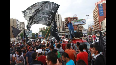 """Protesters carry flags that read """"There is no God but Allah, Mohammed is Allah's messenger"""" and chant during a protest in Tripoli, Lebanon, on Thursday."""