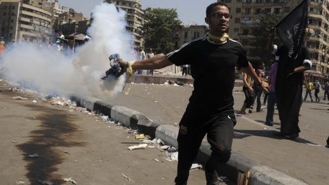 An Egyptian protester throws a tear gas canister toward riot police during clashes near the U.S. Embassy in Cairo on Friday.