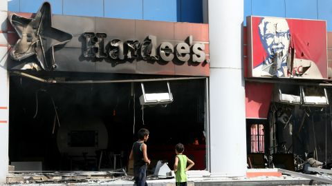 Boys inspect fast food chains Hardee's and KFC after they were torched during a protest in the northern Lebanese city of Tripoli on Friday.
