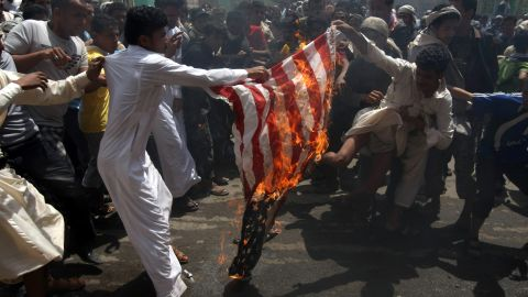 Yemeni protesters burn a U.S. flag on a street leading to the U.S. Embassy in Sanaa on Friday, September 14.