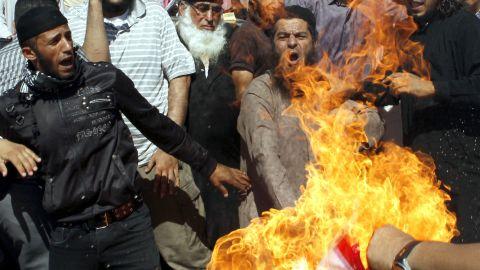 Jordanian protesters burn a U.S. flag near the U.S. Embassy in Amman on Friday.