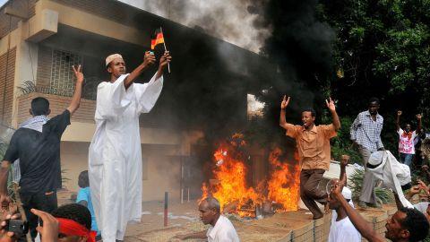 A Sudanese demonstrator burns a German flag after torching the German embassy in Khartoum on September 14, 2012