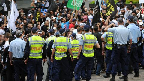 Police stand guard near protesters near the U.S. Consulate General in Sydney on Saturday, September 15.