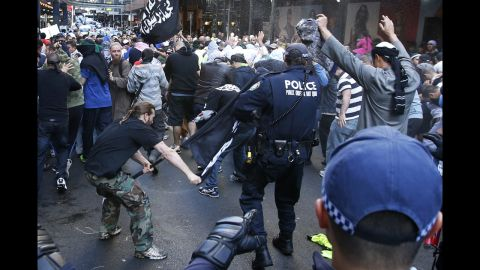 """A protester hits a policeman with a pole in Sydney's central business district on Saturday, September 15. Anger over an anti-Islam video, """"The Innocence of Muslims,"""" spread to Australia on Saturday, and protesters took to the streets of the country's capital."""