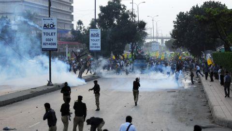 Pakistani police fire tear gas shells toward the protesters in Karachi on Sunday.