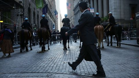 A man walks by a police blockade along Wall Street during Occupy Wall Street demonstrations on Monday.
