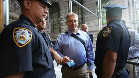 People have their identification checked at a police blockade along Wall Street on Monday.