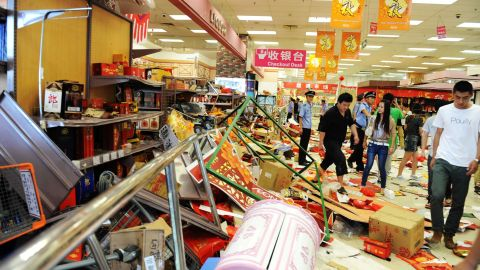 Security guards try to remove Chinese protesters who ransacked Japan's JUSCO departmental store, in Qingdao on September 15.