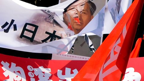 A shredded banner shows Japanese Prime Minister Yoshihiko Noda beside a picture of Mao Zedong in Beijing.