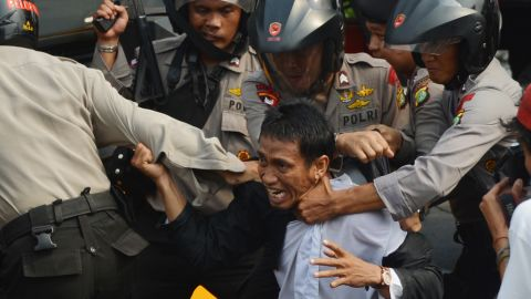 Indonesian anti-riot police arrest a protester Monday outside the U.S. Embassy in Jakarta. Monday's demonstrations come nearly a week after protests erupted in Egypt and Libya, spreading to more than 20 nations.