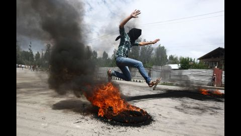 A Kashmiri Muslim boy jumps over a burning tire set up as a roadblock during Tuesday's demonstration Srinagar.