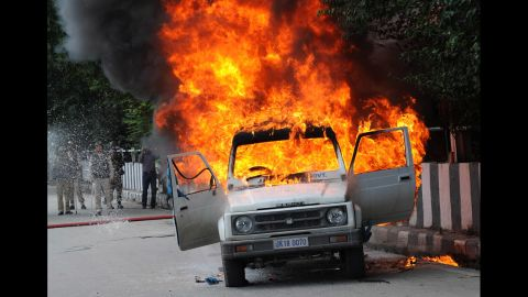 Firefighters attempt to extinguish the flames in an Indian police vehicle  as protesters clash with police during a protest and in Srinagar, Kashmir, on Tuesday.