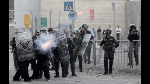 Israeli border policemen fire tear gas toward Palestinian protesters on Tuesday.