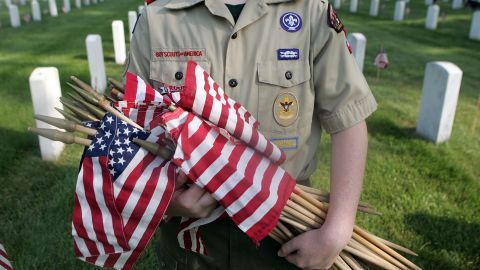 A Boy Scout holds flags that he and other Scouts are going to place on graves at a cemetery in Louisville, Kentucky.