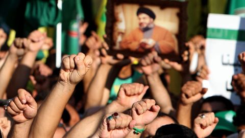 """Supporters of Hezbollah hold a picture depicting Hezbollah leader Hassan Nasrallah and chant the slogan """"God is Great"""" during a mass rally in Tyre, Lebanon, on Wednesday. Thousands of Lebanon's Hezbollah followers protested against the United States and France for a film and cartoons mocking the Prophet Mohammed."""