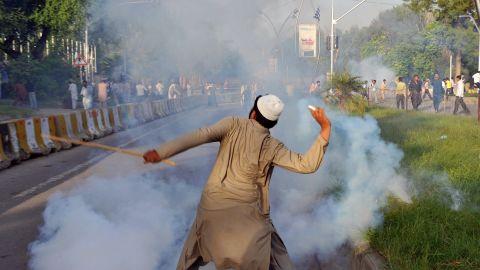 A Pakistani protester throws a tear gas shell back toward police on Thursday.