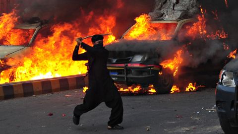 A Pakistani Muslim demonstrator brandishes a stick near burning police vehicles during a protest against an anti-Islam film in Karachi on September 21, 2012. At least nine people died in Pakistan during violent protests on Friday condemning a US-made film insulting Islam, officials said. AFP PHOTO / ASIF HASSAN (Photo credit should read ASIF HASSAN/AFP/GettyImages)