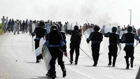 Pakistani riot police chase demonstrators Friday in Islamabad.
