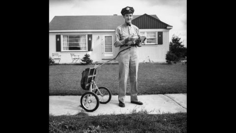 A mail carrier stops on the sidewalk in Michigan in 1955.