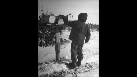 """A Wisconsinite opens the family mailbox in 1946. <a href=""""http://life.time.com/history/the-postal-service-classic-photos/#1"""" target=""""_blank"""" target=""""_blank"""">See more photos of the classic Postal Service from Life.com</a>."""