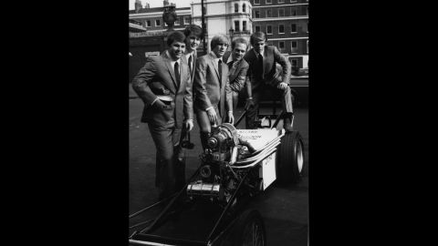 """The Beach Boys pose around a dragster in London's West End during a visit to England in 1964 to promote their new single 'When I Grow Up"""" in November 1964"""