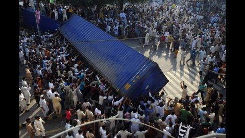 Pakistani Muslim demonstrators topple a freight container that was placed by police to block a street during a protest on Friday.