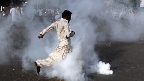 A demonstrator kicks a tear gas shell in Karachi, Pakistan, on Friday.