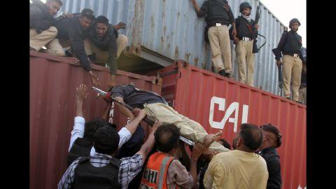 Pakistani policemen help an injured comrade Friday in Karachi.